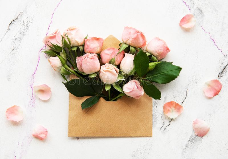 Envelope and pink roses. On a white marble background royalty free stock images