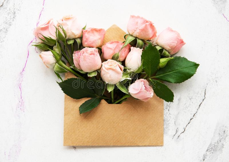 Envelope and pink roses. On a white marble background stock photo