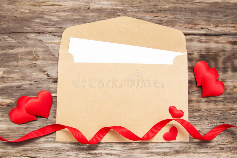 Envelope with red fabric hearts. And ribbon on a old wooden background stock photography