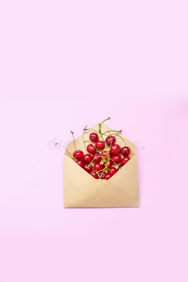 Envelope with ripe red cherry berries on a pink background. Invitation card, flat lay. Food concept. Food concept. Envelope with ripe red cherry berries on a royalty free stock images