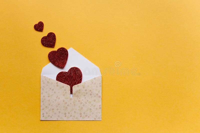 Envelope with symbols in the form of red hearts on a yellow background. Celebration. stock photography