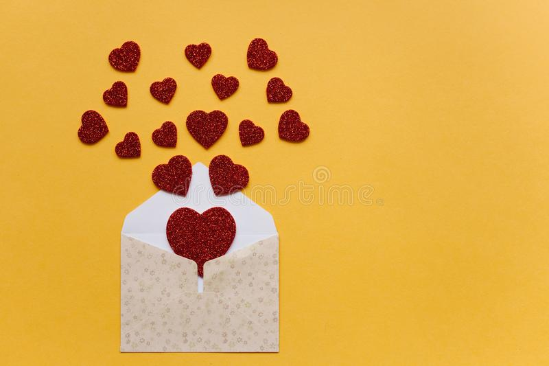 Envelope with symbols in the form of red hearts on a yellow background. Celebration. royalty free stock images