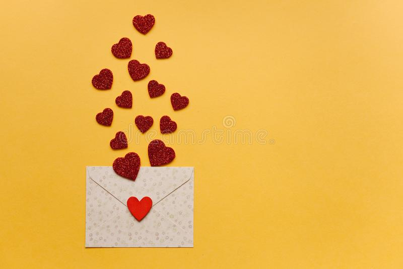 Envelope with symbols in the form of red hearts on a yellow background. Celebration. royalty free stock image