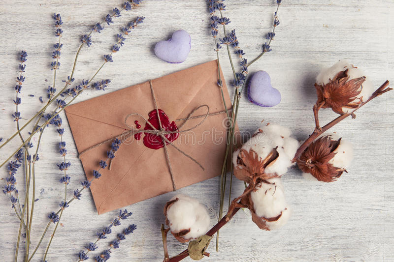 Envelope with wax seal and lavender on wooden background. Envelope with wax seal on wooden background. Flower lavender and heart shaped macaroons cookies royalty free stock image