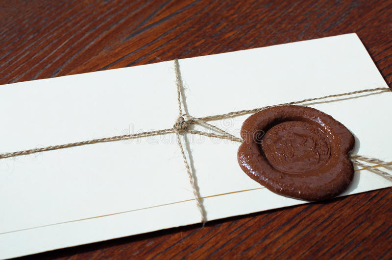 Envelope with a wax seal on a wooden table stock image