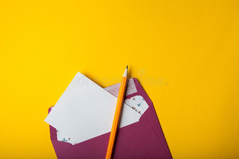 Envelope, white sheet of paper and pencil on a yellow background royalty free stock photo