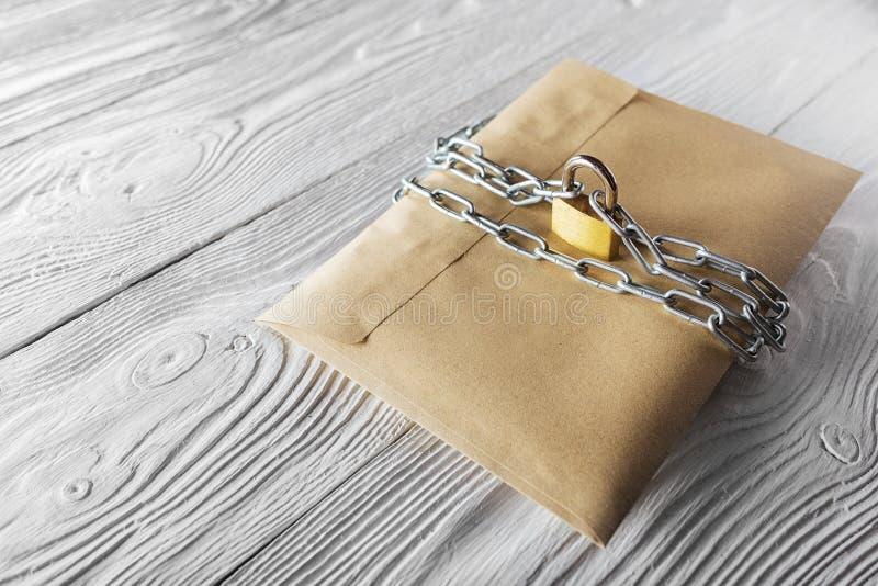 Envelopes de Kraft com letras e cadeado, corrente no fundo de madeira branco velho Proteção de seu cargo, enviamento do PC Placas foto de stock royalty free