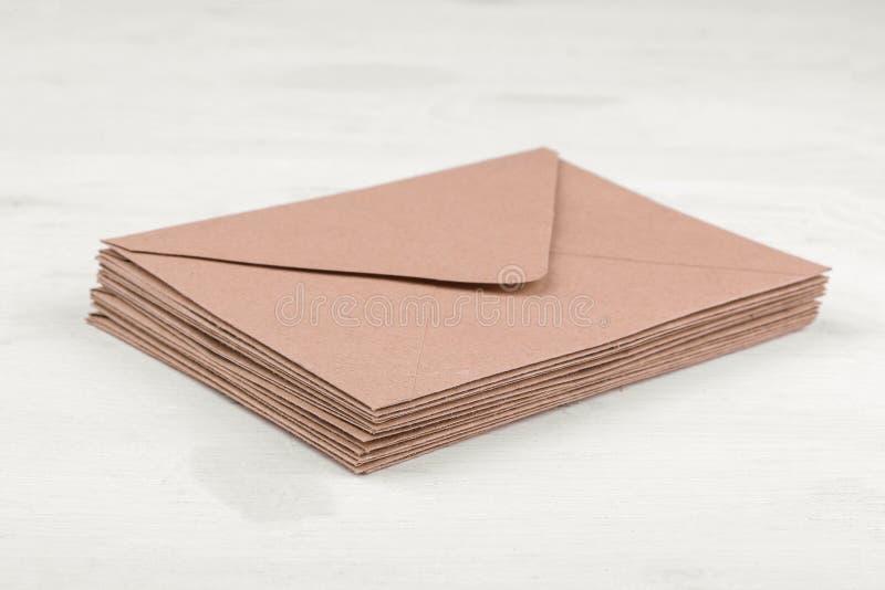 Envelopes do papel de embalagem em uma tabela de madeira branca Conceito do correio ou da entrega imagem de stock