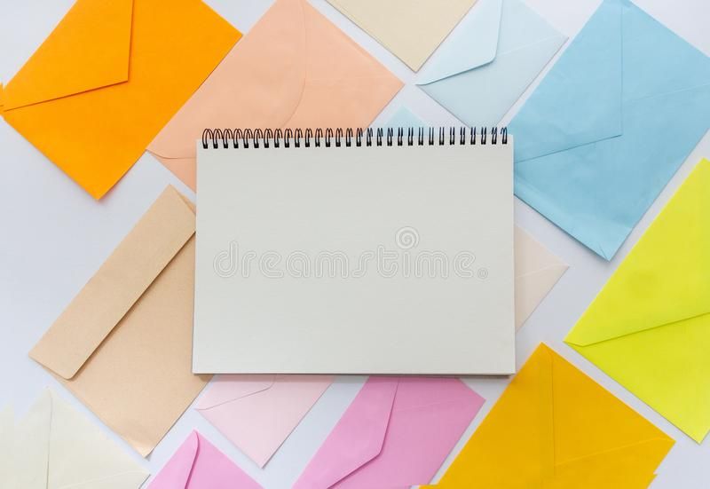 Envelopes in pastel colors align in oblique style with a blank white sketchbook. Blank white sketchbook with envelopes in pastel colors align in oblique style royalty free stock photo