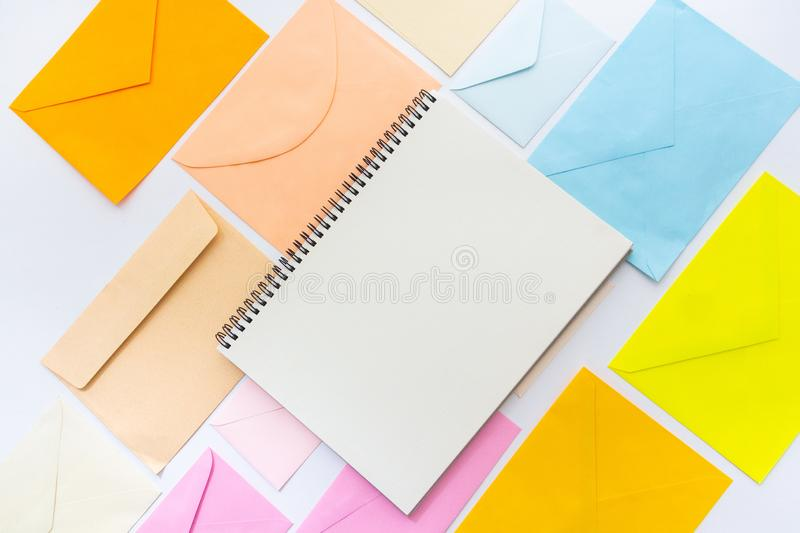 Envelopes in pastel colors align in oblique style with a blank white sketchbook. Blank white sketchbook with  envelopes in pastel colors align in oblique style stock photos