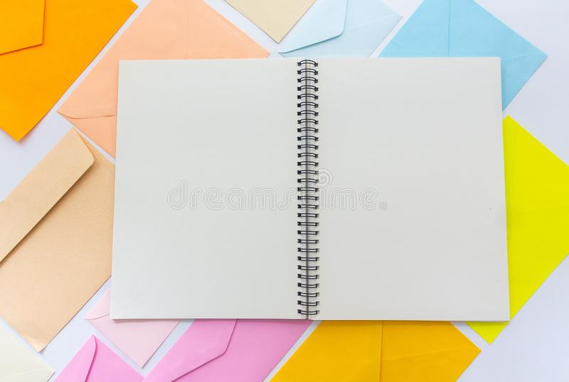 Envelopes in pastel colors align in oblique style with a blank white sketchbook. Blank white open sketchbook with  envelopes in pastel colors align in oblique royalty free stock images