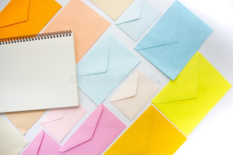 Envelopes in pastel colors align in oblique style with a blank white sketchbook. Envelopes in pastel colors align in oblique style with a copy-space stock photo
