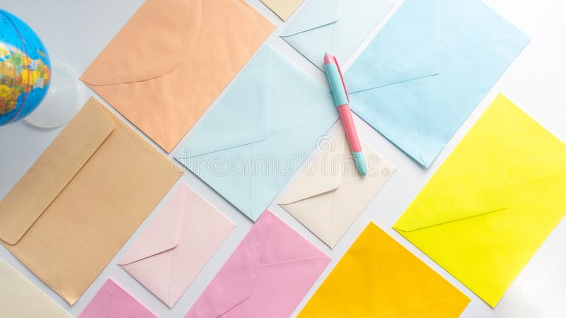 Envelopes in pastel colors align in oblique style with a globe on the left corner and a pen. Envelopes in pastel colors align in oblique style with a globe on royalty free stock image