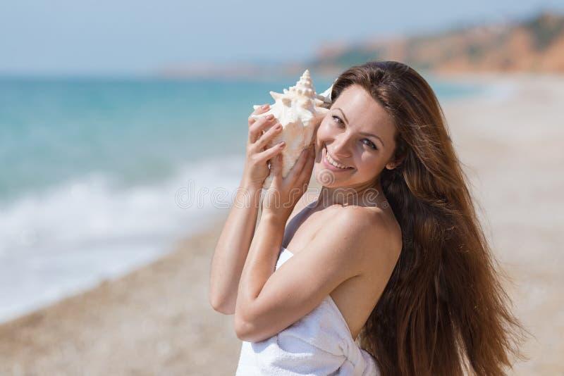 Enveloppé dans la fille de serviette tient la coquille de mollusque et écoute il image libre de droits