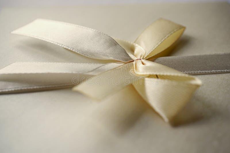 Enveloppe argentée carrée avec le ruban nacré et chignon comme un exemple de couverture typique d'invitation de mariage et d'anno photo stock