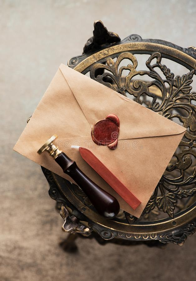 Enveloppe avec le joint de cire, le joint de cire et la cire de cachetage pour des timbres sur la table de bronze de cru photos stock