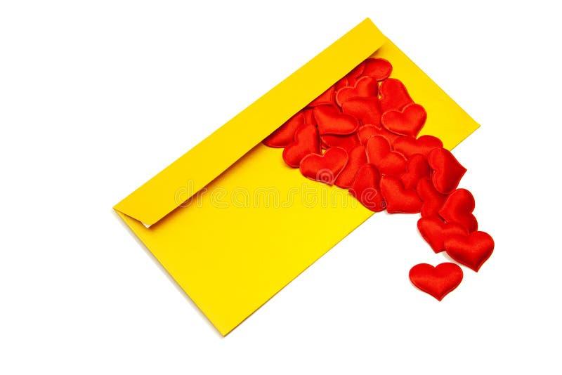 Enveloppe d'or et coeurs rouges rampant hors de elle Sur un fond blanc d'isolement, le concept de l'amour dans la distance photo libre de droits