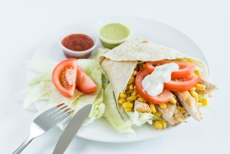 Enveloppe de Burrito avec la tomate, le maïs, la laitue, le poulet, la mayonnaise et les sauces avec le fond blanc photographie stock