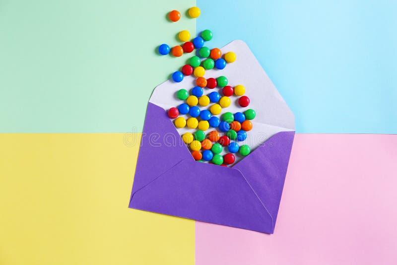Enveloppe de courrier avec des sucreries sur le fond de couleur photographie stock