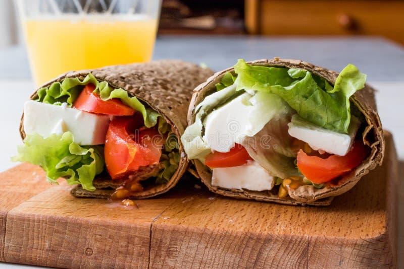 Enveloppe de régime faible en calories avec du fromage, les tomates, la salade et le jus d'orange photographie stock libre de droits