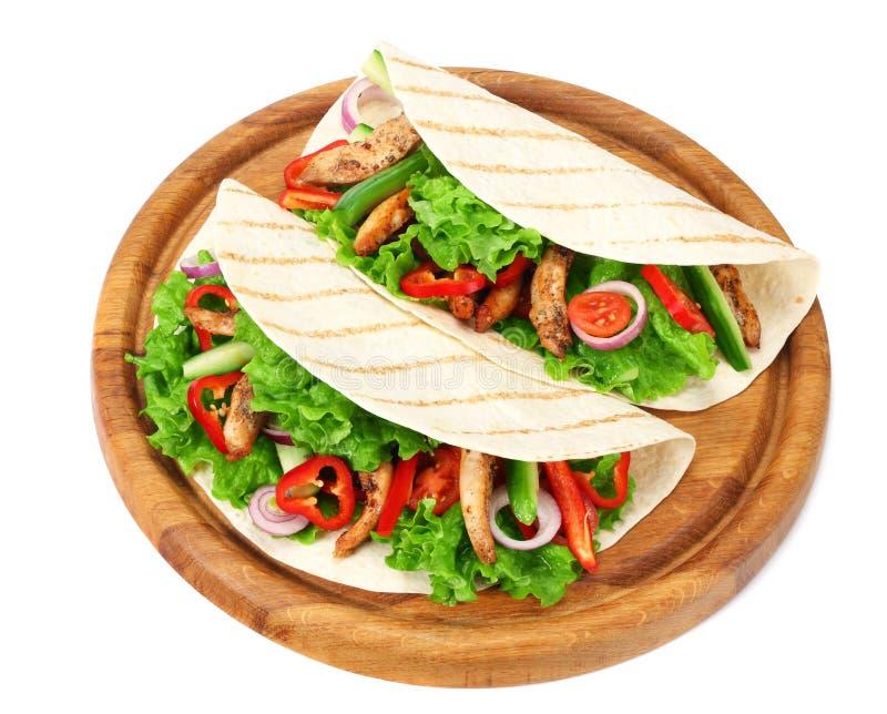 Enveloppe de tortilla avec de la viande et des l?gumes de poulet frit sur le conseil en bois d'isolement sur le fond blanc image stock