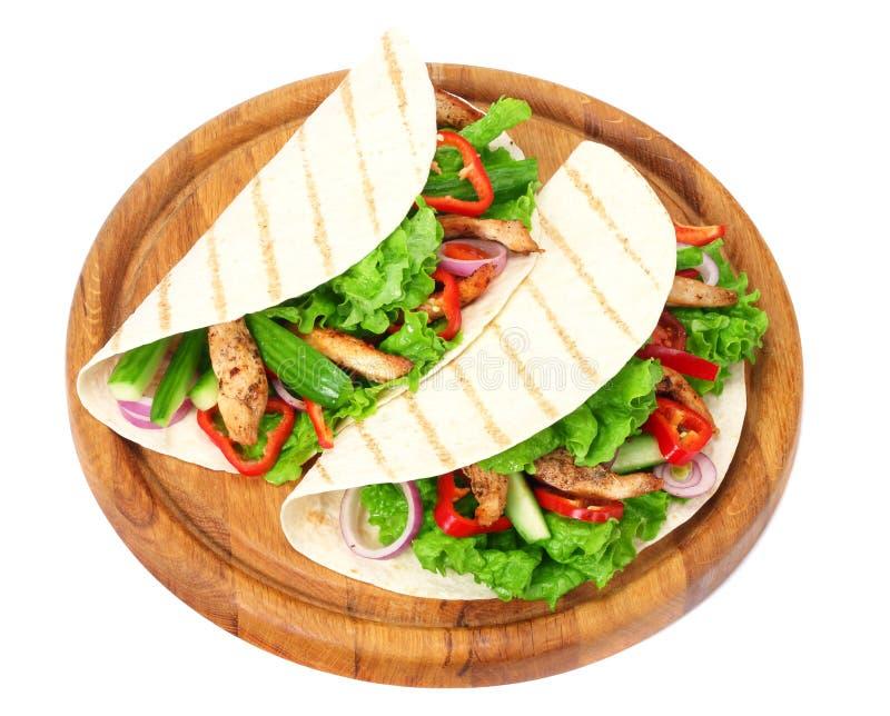 Enveloppe de tortilla avec de la viande et des l?gumes de poulet frit sur le conseil en bois d'isolement sur le fond blanc photographie stock libre de droits