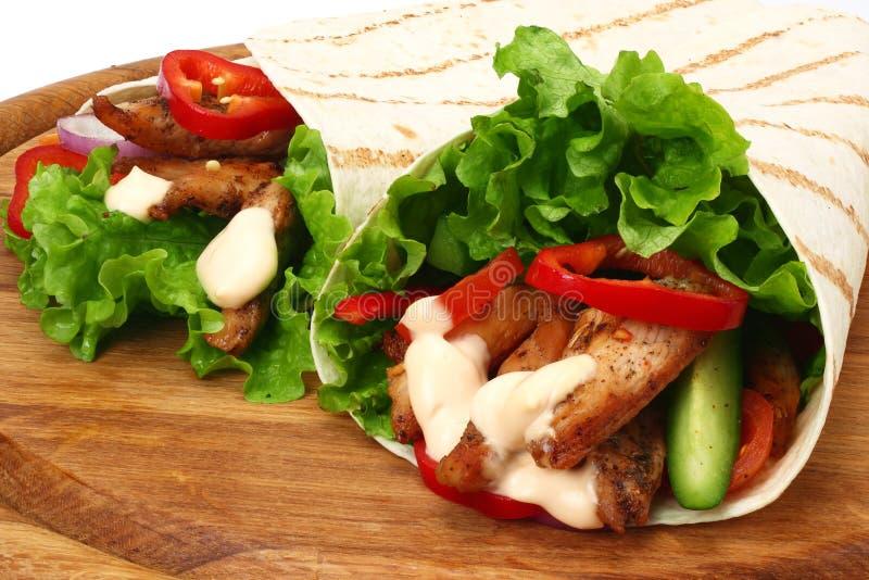 Enveloppe de tortilla avec de la viande et des l?gumes de poulet frit sur le conseil en bois d'isolement sur le fond blanc photos stock