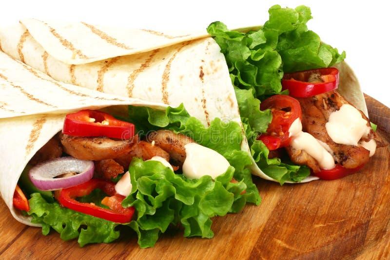 Enveloppe de tortilla avec de la viande et des l?gumes de poulet frit sur le conseil en bois d'isolement sur le fond blanc photo libre de droits