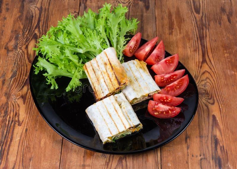 Enveloppe, laitue et tomates grillées de salade de viande sur le plat noir photos stock