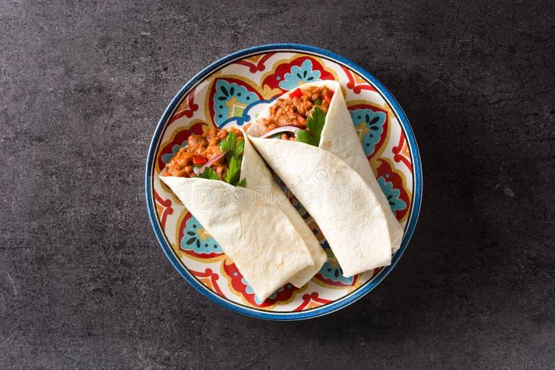 Enveloppe mexicaine typique de burrito avec du boeuf, des frijoles et des légumes sur le fond noir images libres de droits