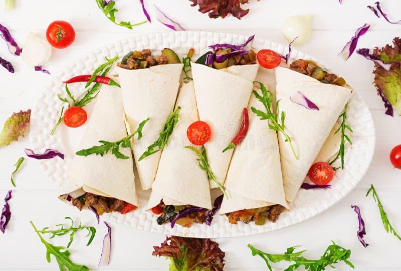 Enveloppes de Burritos avec du boeuf et des légumes sur un fond clair photos stock