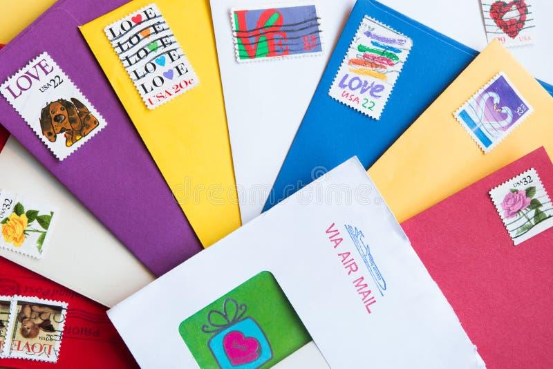 Enveloppes de différentes couleurs avec des timbres d'amour photos stock