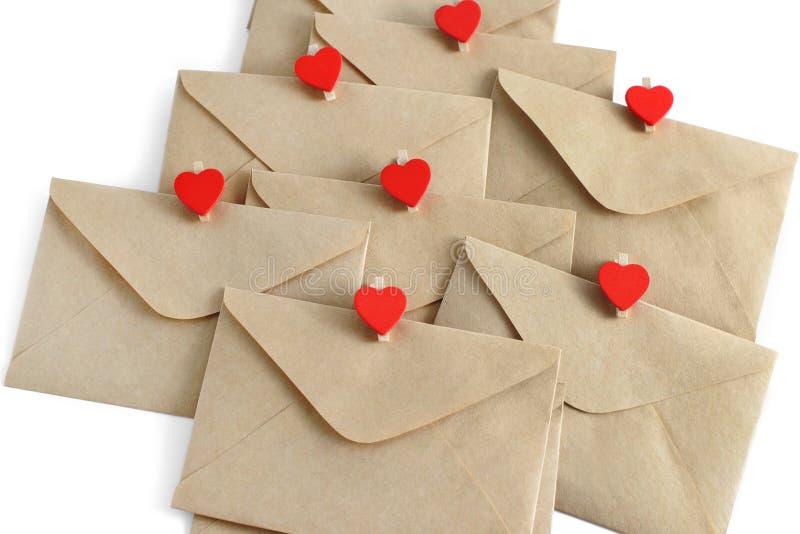 Enveloppes de papier de métier avec les goupilles rouges de coeur d'isolement sur le fond blanc image libre de droits