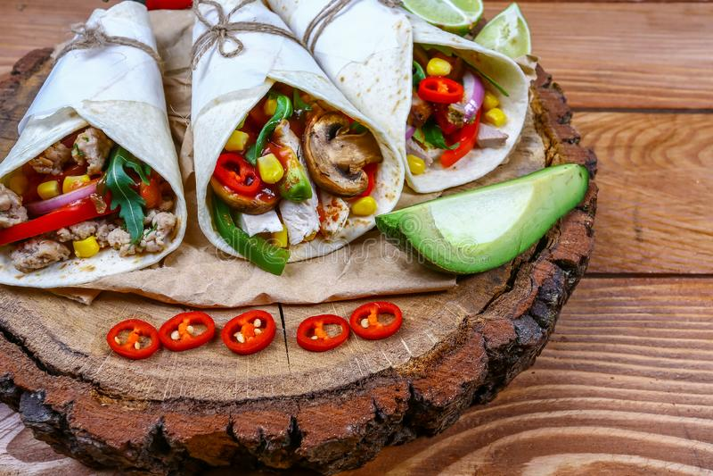 Enveloppes de salade de César de poulet avec le lard, les haricots d'avocat, les tomates, la laitue et le fromage La tortilla, bu images stock