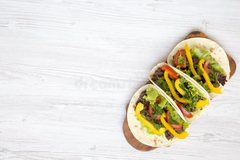 Enveloppes de tortilla avec de la viande grillée de boeuf, salade, persil, tomate, poivre sur le conseil en bois images libres de droits