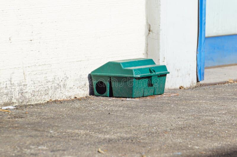 Envenene la caja de la trampa de rata en piso cerca de la pared fotos de archivo