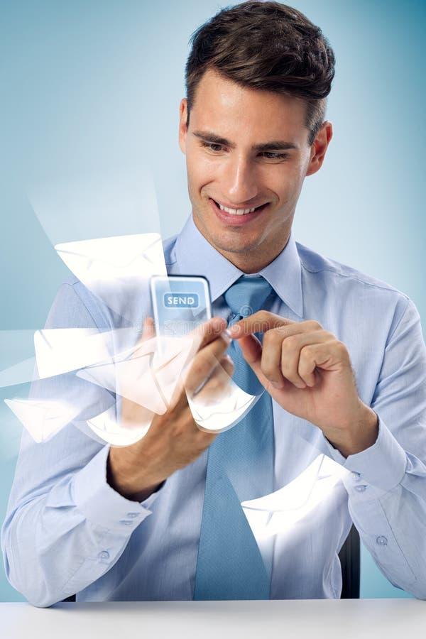Enviando o correio - homem de sorriso que usa o telefone futurista fotografia de stock royalty free