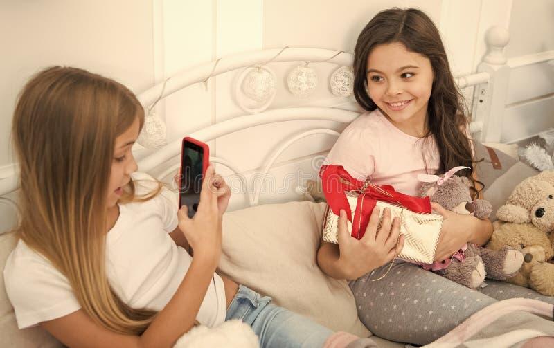 Enviando o v?deo e o pics Crian?as pequenas felizes com telefone celular As meninas pequenas usam o telefone na cama Tomando o Na fotografia de stock royalty free