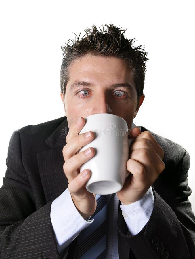 Envicie al hombre de negocios en traje y ate la taza de consumición de café ansiosa y loca en el apego del cafeína foto de archivo