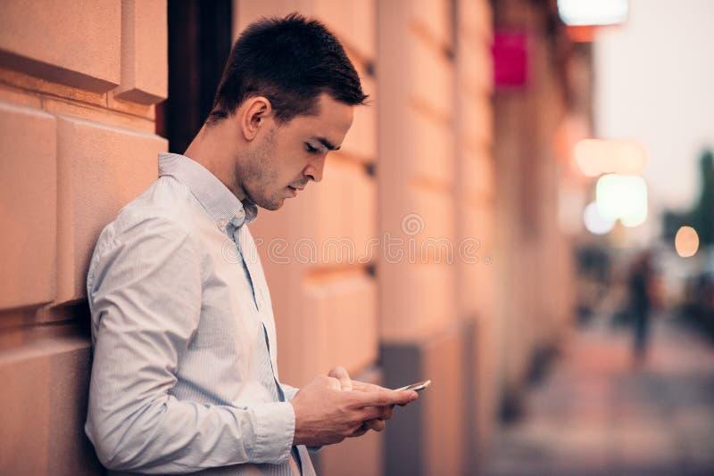Envio de mensagem de texto considerável do homem novo em uma rua da cidade imagens de stock royalty free