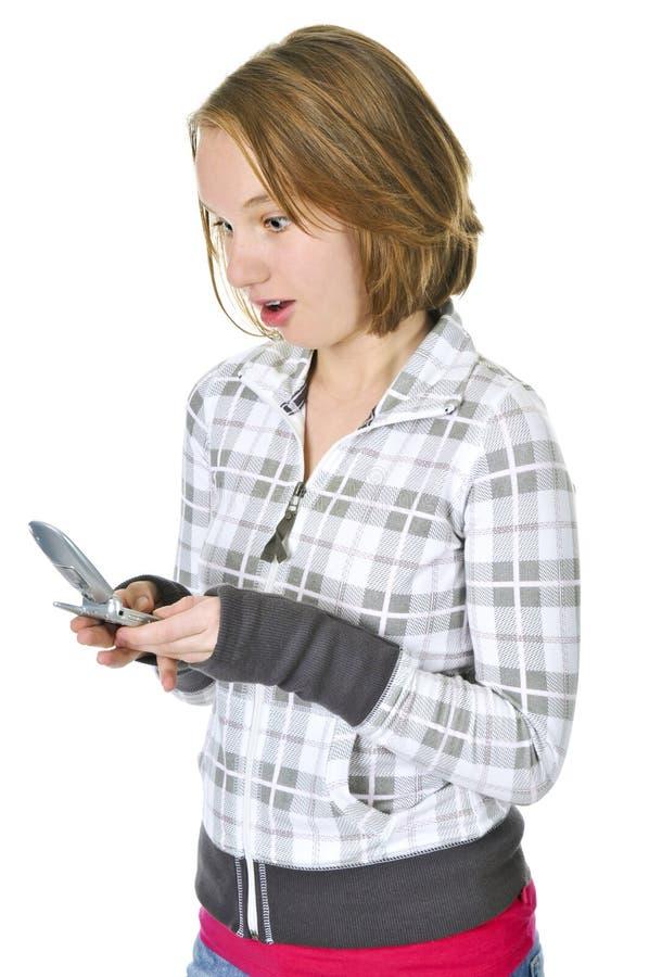 Envio de mensagem de texto do adolescente em um telefone de pilha fotografia de stock
