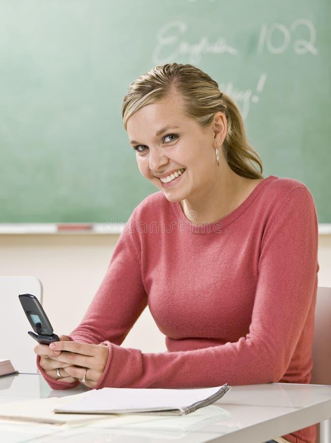 Envio de mensagem de texto do estudante no telefone de pilha na sala de aula imagem de stock royalty free