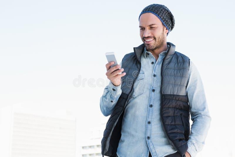 Envio de mensagem de texto do homem novo no telefone celular fotos de stock