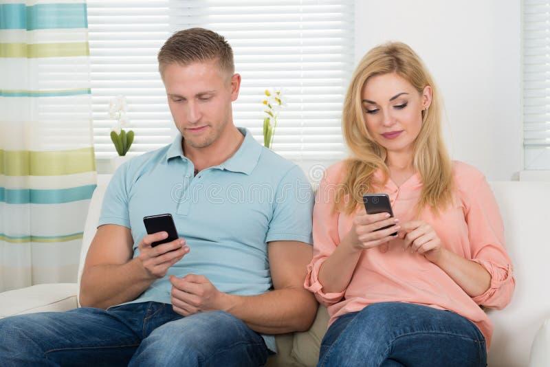 Envio de mensagem de texto dos pares através dos telefones celulares no sofá fotografia de stock