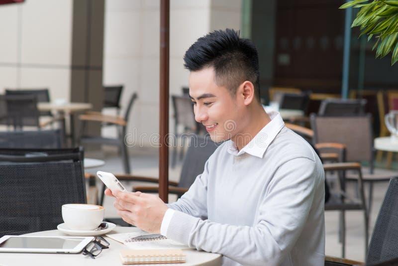 Envio de mensagem de texto feliz asiático novo do homem na aplicação social dos meios pelo smartphone durante o tempo no café, es fotos de stock royalty free