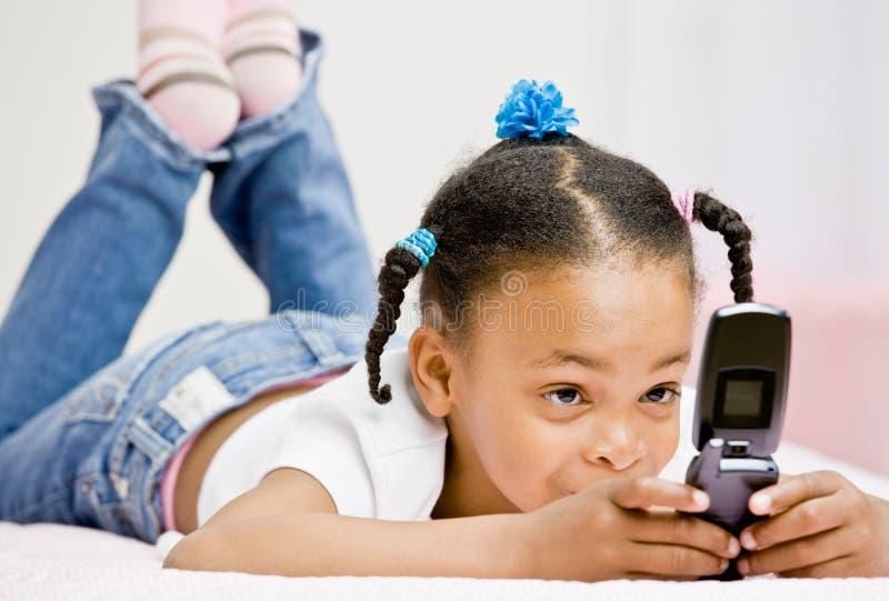 Envio de mensagem de texto feliz da menina no telefone de pilha fotografia de stock