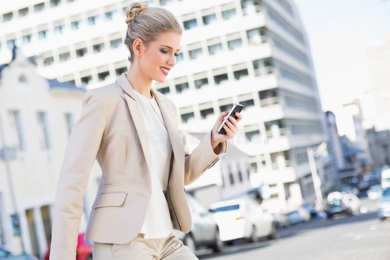 Envio de mensagem de texto lindo de sorriso da mulher de negócios fotografia de stock