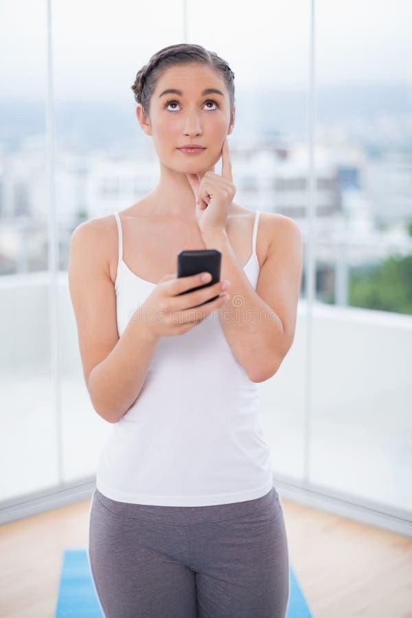 Envio de mensagem de texto moreno desportivo pensativo imagens de stock