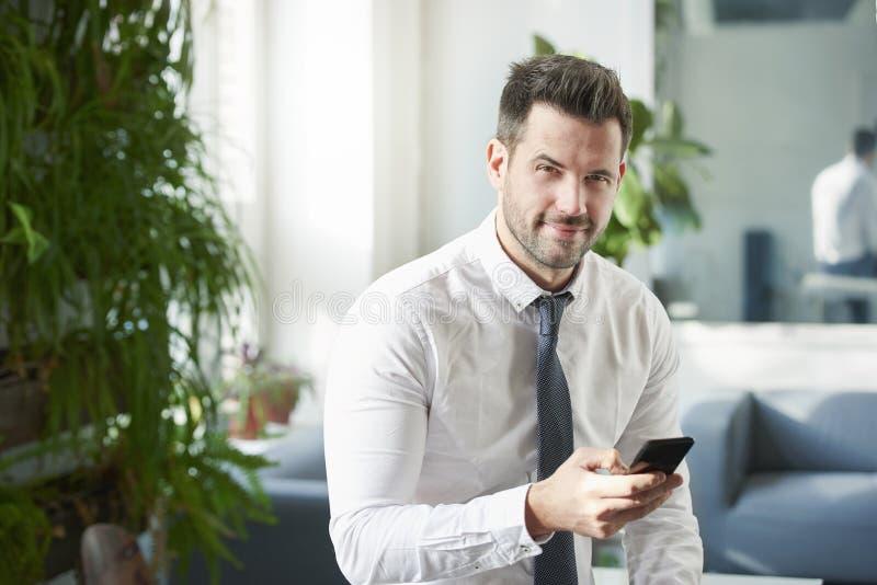 Envio de mensagem de texto do homem de negócios ao sentar-se no offce imagem de stock