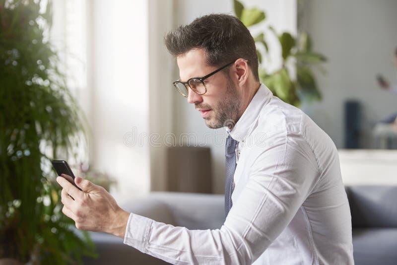 Envio de mensagem de texto do homem de neg?cios ao sentar-se no offce imagens de stock
